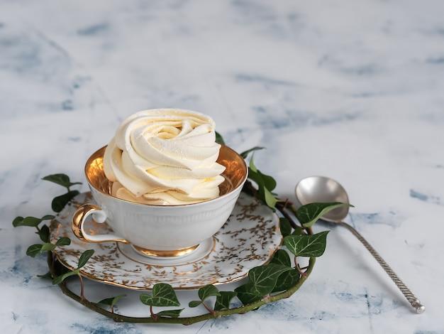 Marshmallow de damasco em um copo cercado por um ramo de hera está localizado. zéfiro caseiro, close-up.