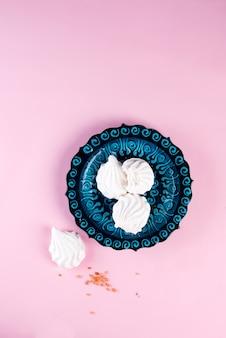 Marshmallow delicioso no prato azul turco isolado na configuração rosa, plana