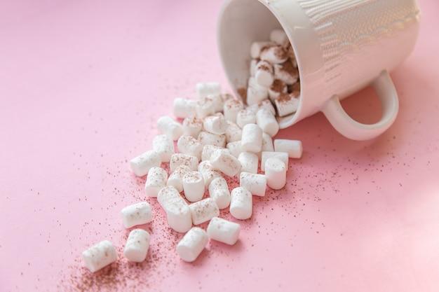 Marshmallow derramado de uma caneca branca em um rosa pastel