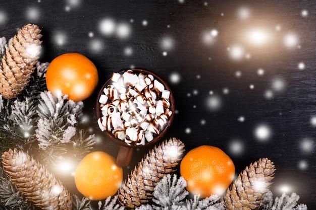 Marshmallow doce de comida de natal com chocolate no copo marrom sobre fundo preto.