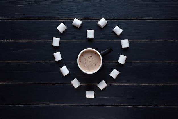 Marshmallow em forma de coração e chocolate quente em uma mesa de madeira preta