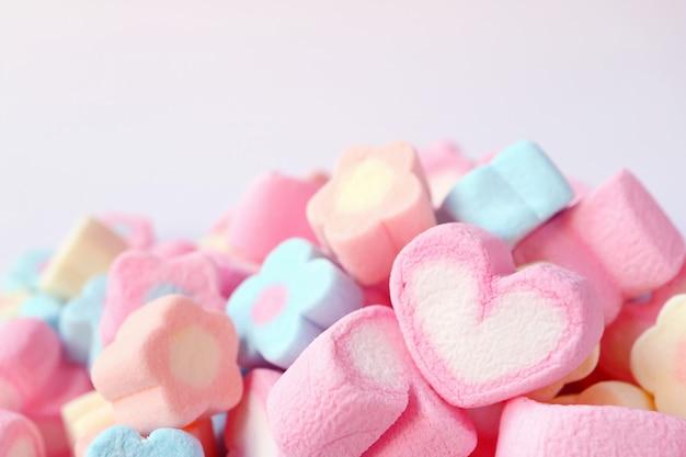Marshmallow em forma de coração rosa e branco na pilha de cor pastel marshmallow em forma de flor