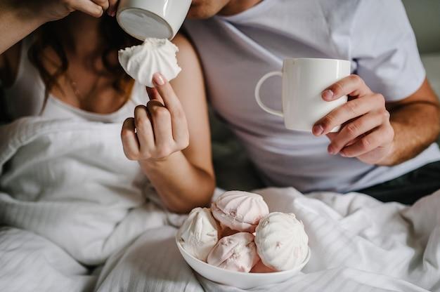 Marshmallow na mão ao fundo, homem e mulher bebem café na cama