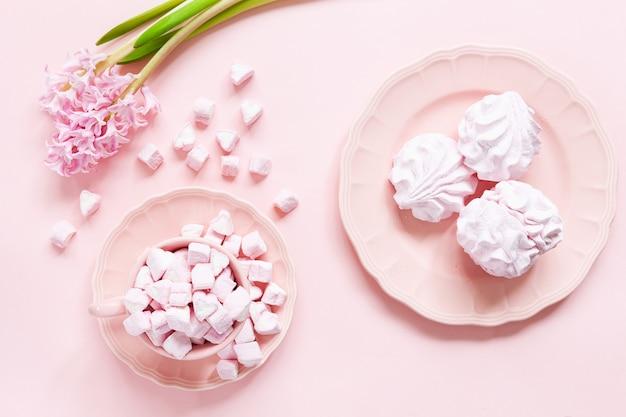 Marshmallow rosa e merengue rosa em pratos cor de rosa