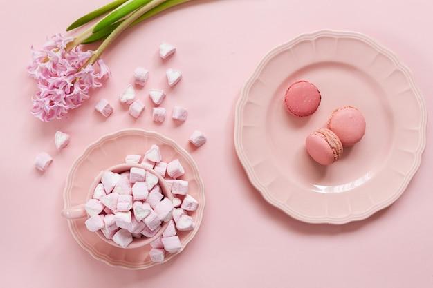 Marshmallow rosa e rosa macaroons em pratos rosa