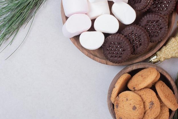 Marshmallows, biscoitos na placa de madeira na mesa branca.