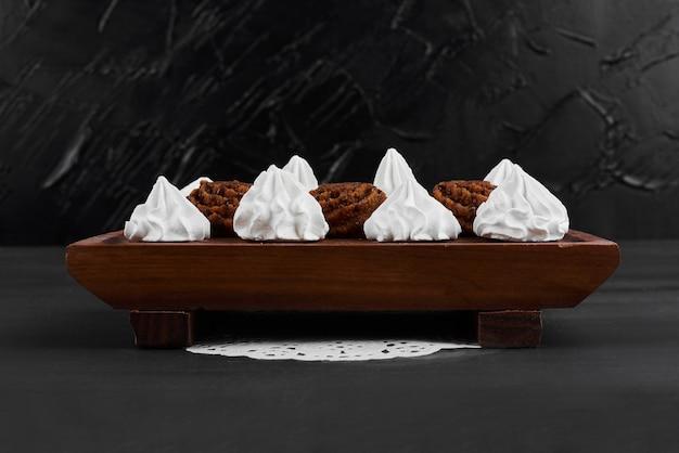 Marshmallows brancos com bombons de cacau em uma bandeja de madeira.