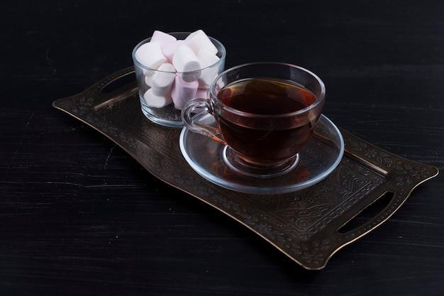 Marshmallows brancos com uma xícara de chá.