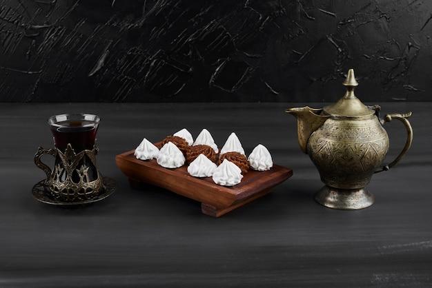 Marshmallows brancos e bombons de cacau em uma travessa de madeira com um copo de chá.