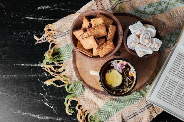 Marshmallows brancos em uma xícara metálica com chá de ervas e biscoitos.