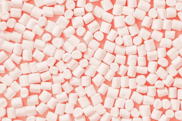 Marshmallows brancos no fundo pastel da cor na moda. lay plana