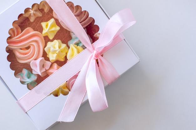 Marshmallows caseiros de cores diferentes são lindamente embalados em uma caixa de presente.
