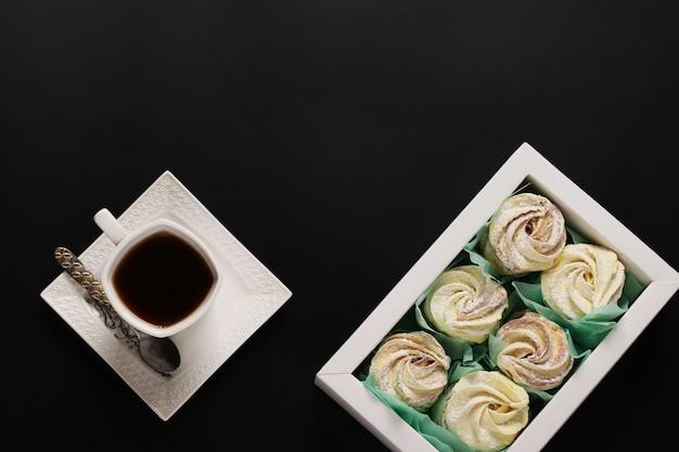 Marshmallows caseiros de zéfiro em uma caixa e xícara de café em um fundo escuro, vista superior