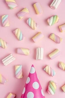 Marshmallows coloridos com chapéu de festa em fundo rosa