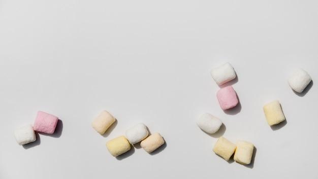 Marshmallows coloridos contra um pano de fundo branco