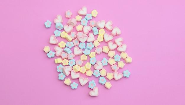Marshmallows coloridos de flatlay sobre fundo rosa doce com espaço de cópia