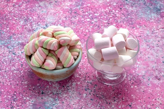 Marshmallows coloridos doces de vista frontal pouco formados dentro de um pote redondo com brancos na mesa rosa.