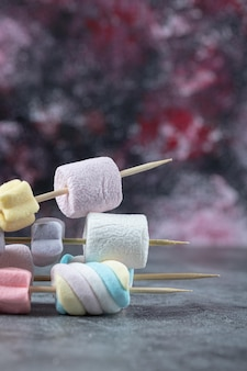 Marshmallows coloridos em palitos para serem grelhados.