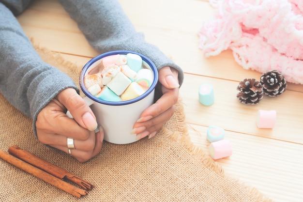 Marshmallows da cor pastel no chocolate quente nas mãos da mulher. comida e bebida