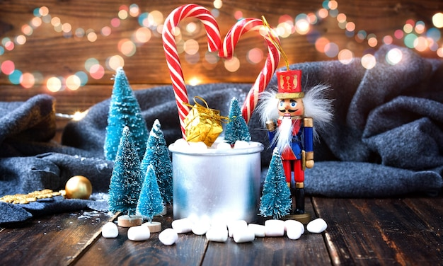 Marshmallows de natal e decorações de ano novo na mesa de madeira com manta cinza. férias de inverno