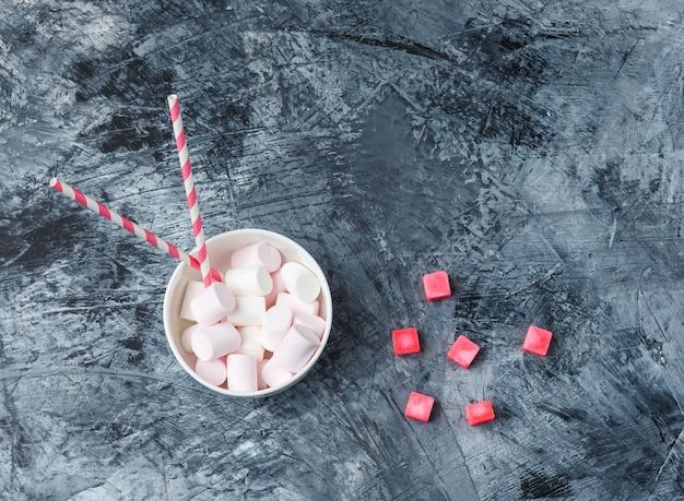 Marshmallows de vista superior com canas de açúcar e doces vermelhos na superfície de mármore azul escuro. horizontal