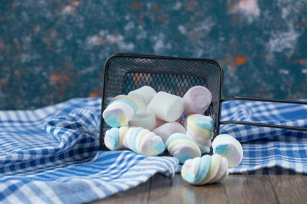 Marshmallows deliciosos multicoloridos na mini cesta metálica.