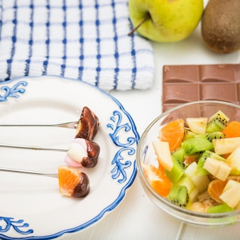 Marshmallows diferentes em um belo prato sobre os garfos.