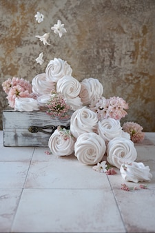 Marshmallows do russo e flores da mola na caixa de madeira do vintage. voando flores