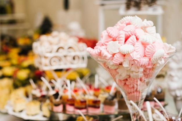 Marshmallows doces em um copo com fundo desfocado