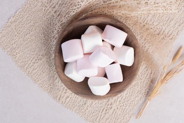 Marshmallows doces na placa de madeira sobre serapilheira