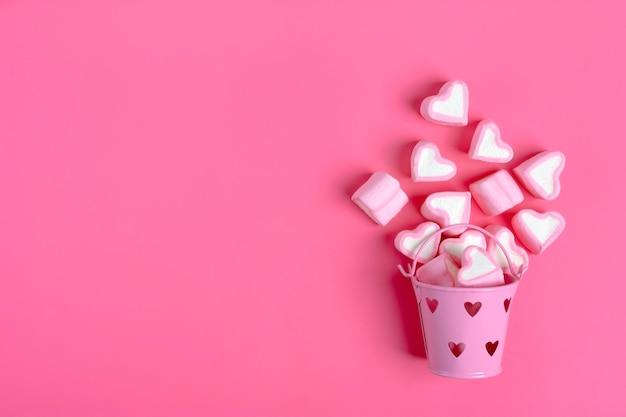 Marshmallows em forma de coração derramado de fundo de rosa-de-rosa balde de ferro feliz dia dos namorados