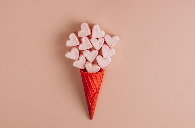 Marshmallows em forma de coração rosa e branco com cone de waffle no fundo rosa. vista do topo. copie o espaço