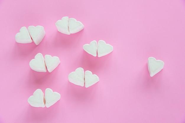 Marshmallows em formas de coração para dia dos namorados sobre fundo de papel rosa