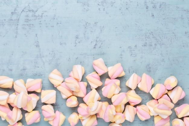 Marshmallows em fundo azul com copyspace. camada plana ou vista superior. plano de fundo ou textura de mini marshmallows coloridos.