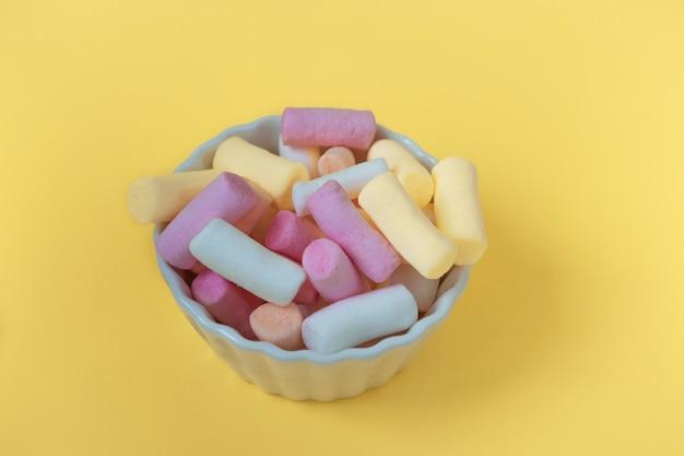 Marshmallows multicoloridos em uma tigela sobre um fundo amarelo. maquete da embalagem, cartão postal ou cartão, vista superior em close-up