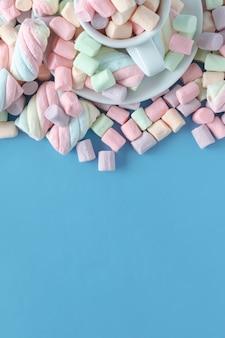 Marshmallows multicoloridos redondos pequenos no backgrouns azuis.