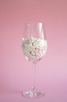 Marshmallows pequenos cor-de-rosa em uma taça de vidro