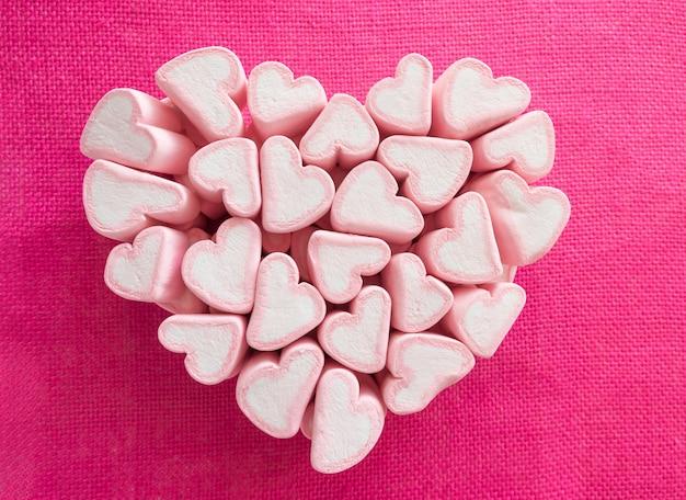 Marshmallows rosa dobrados em forma de um grande coração na lona rosa