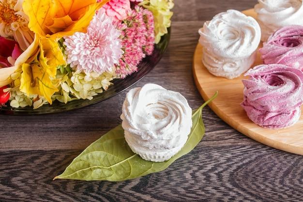 Marshmallows rosa e branco (zéfiro) em uma tábua de madeira redonda com composição floral