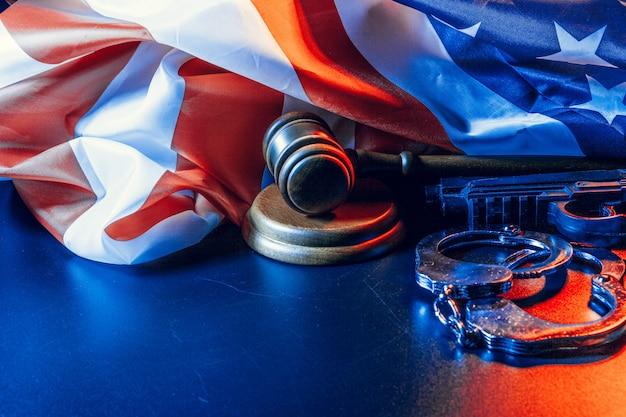 Martelo, algemas e bandeira americana na superfície escura