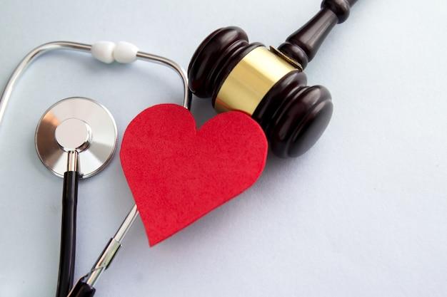 Martelo com coração vermelho, pílulas, estetoscópio e livros na mesa. conceito de direito médico.