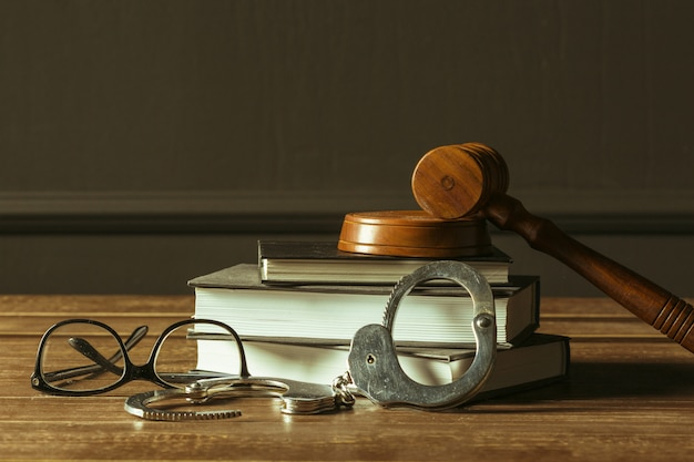 Martelo com livros na velha mesa de madeira