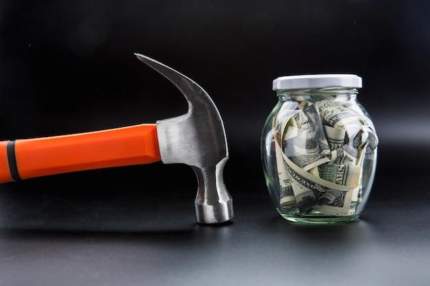 Martelo contra jarro cheio de dólares, economizando dinheiro