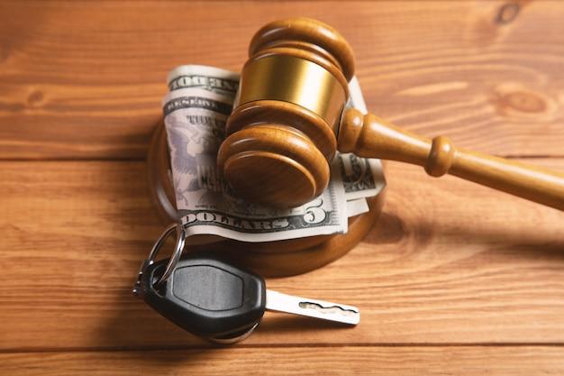 Martelo da corte com dinheiro e as chaves do carro na mesa