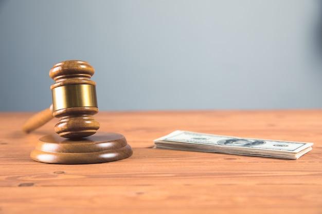 Martelo da corte com dinheiro em uma mesa de madeira