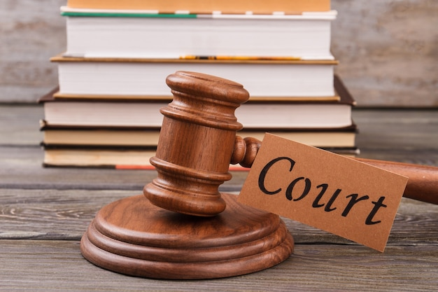 Martelo da corte na frente da pilha de livros. martelo marrom do juiz do close-up e livros de direito.