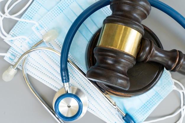 Martelo da lei, estetoscópio e máscaras antivírus no rosto de perto, conceito de direito médico