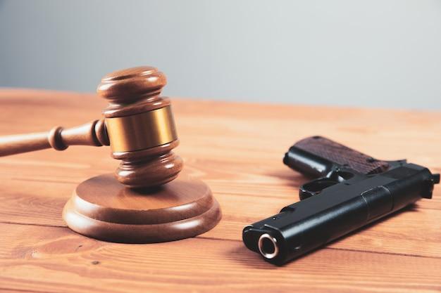 Martelo da quadra com uma pistola na mesa