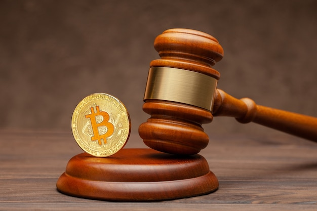 Martelo de bitcoin e juiz sobre fundo marrom de madeira.