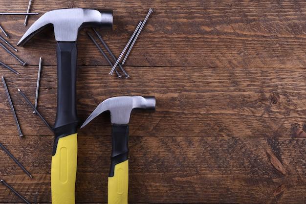 Martelo de ferro e pregos na mesa de madeira
